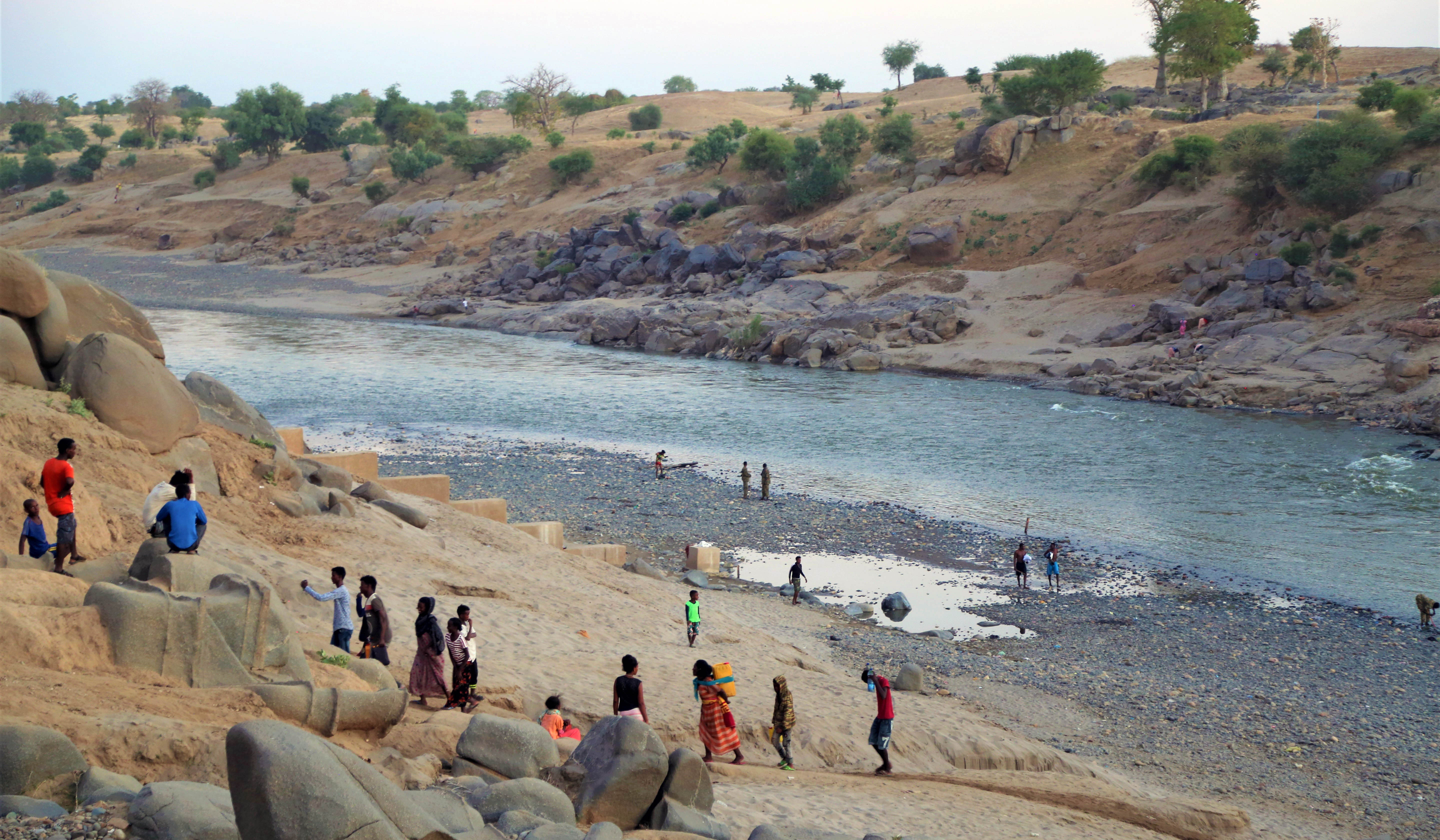 The photo shows refugees walking across an area of water and up a large hill.