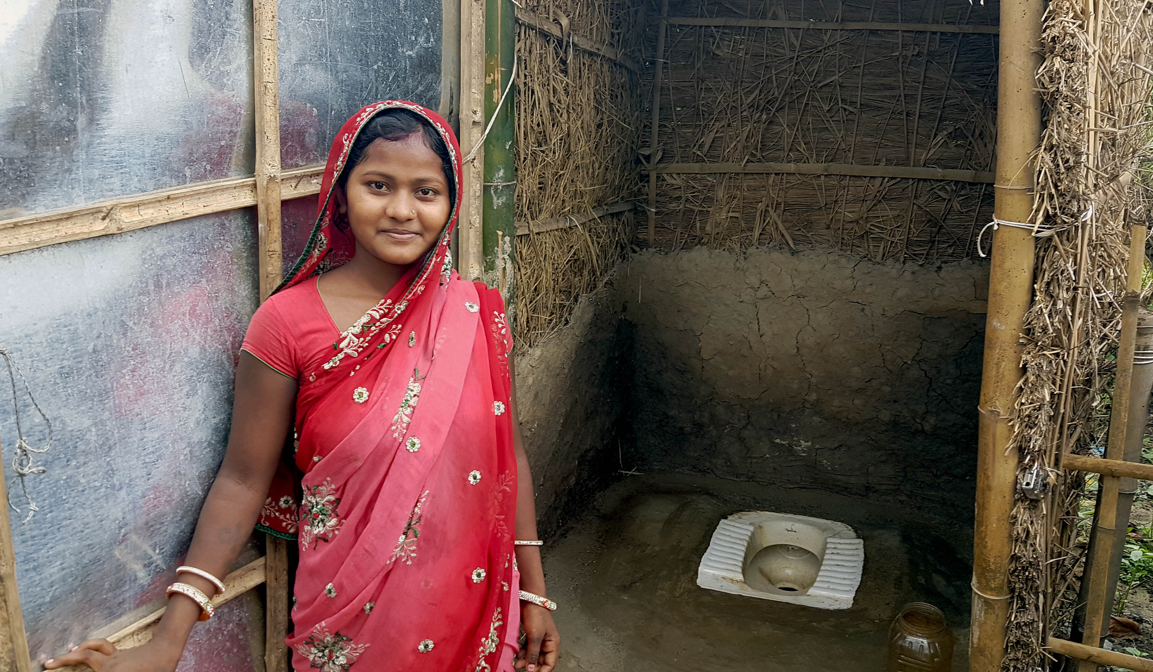 A young girl smiles as she stands in front of a toilets in Belbari.