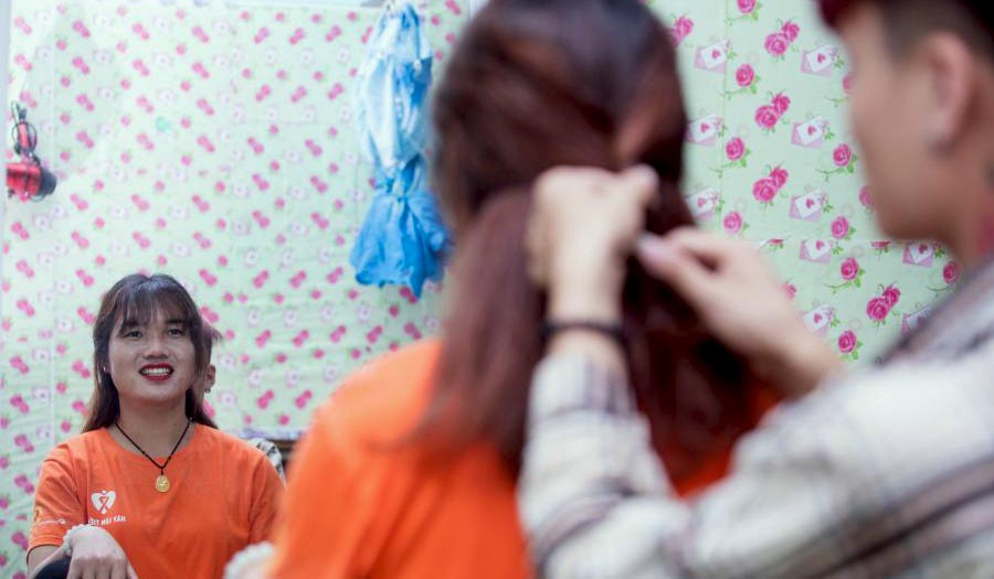 Lo Kim Thuy looks at her reflection as someone braids her hair.