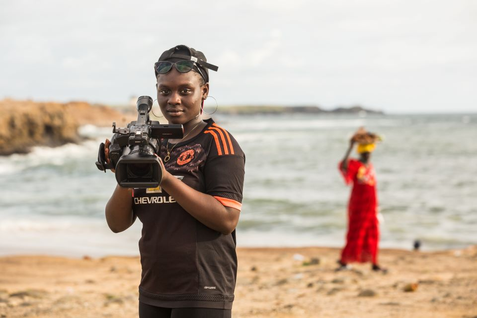 Oumou Kalsoum Diop, 18, poses for a portrait with her video camera on the beach in Dakar.