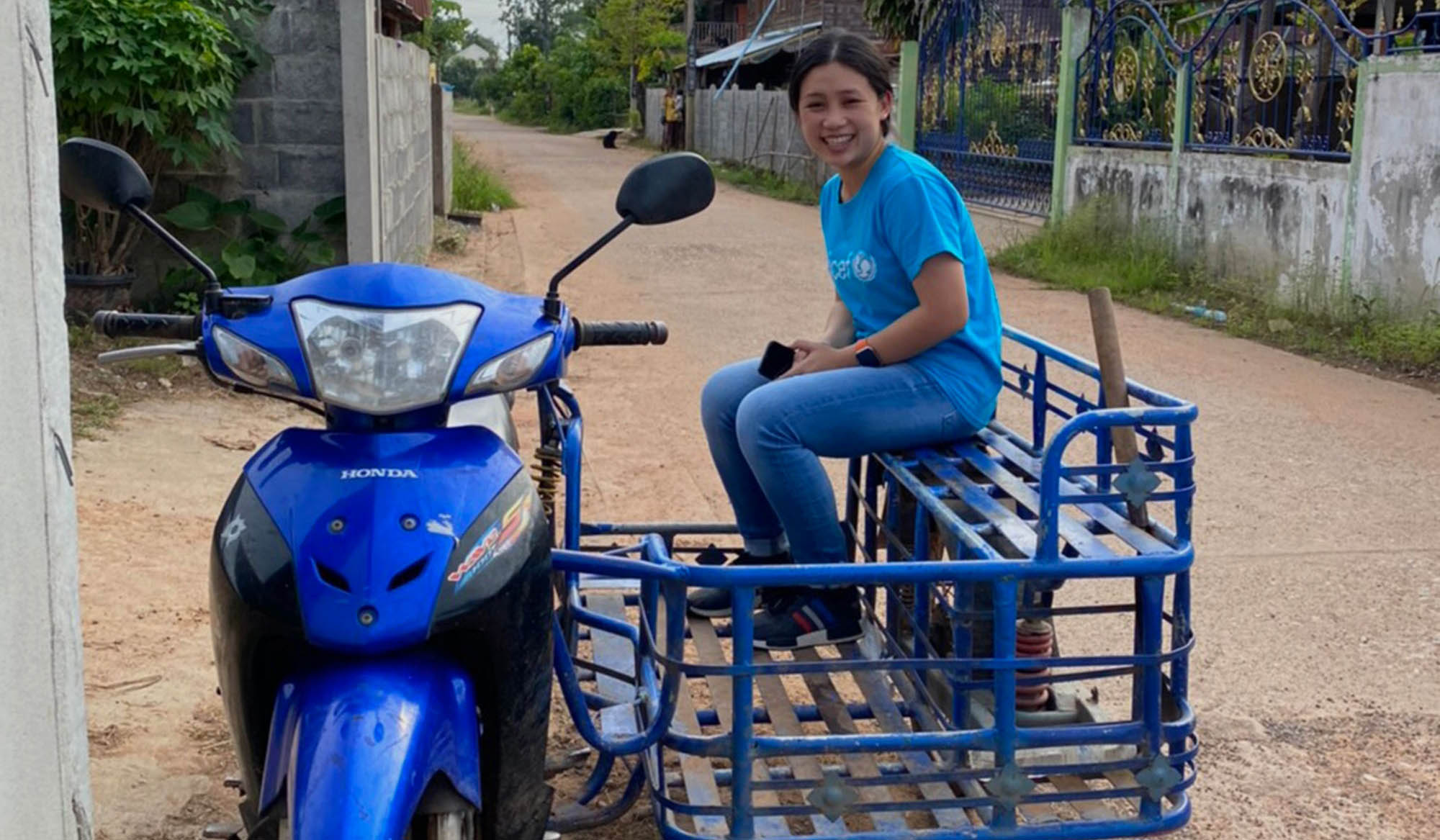 Rasa smiles at the camera as she sits on the side cart of a motorcycle at her work.
