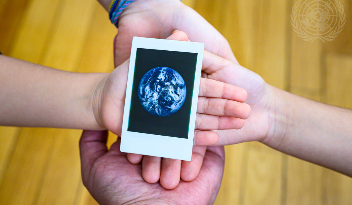 Four hands hold an image of the earth on International Mother Earth Day (22 April).