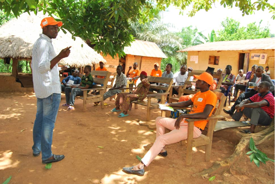 Clement stands in front of a group of men seated as he presents to them issues related to gender-based violence.