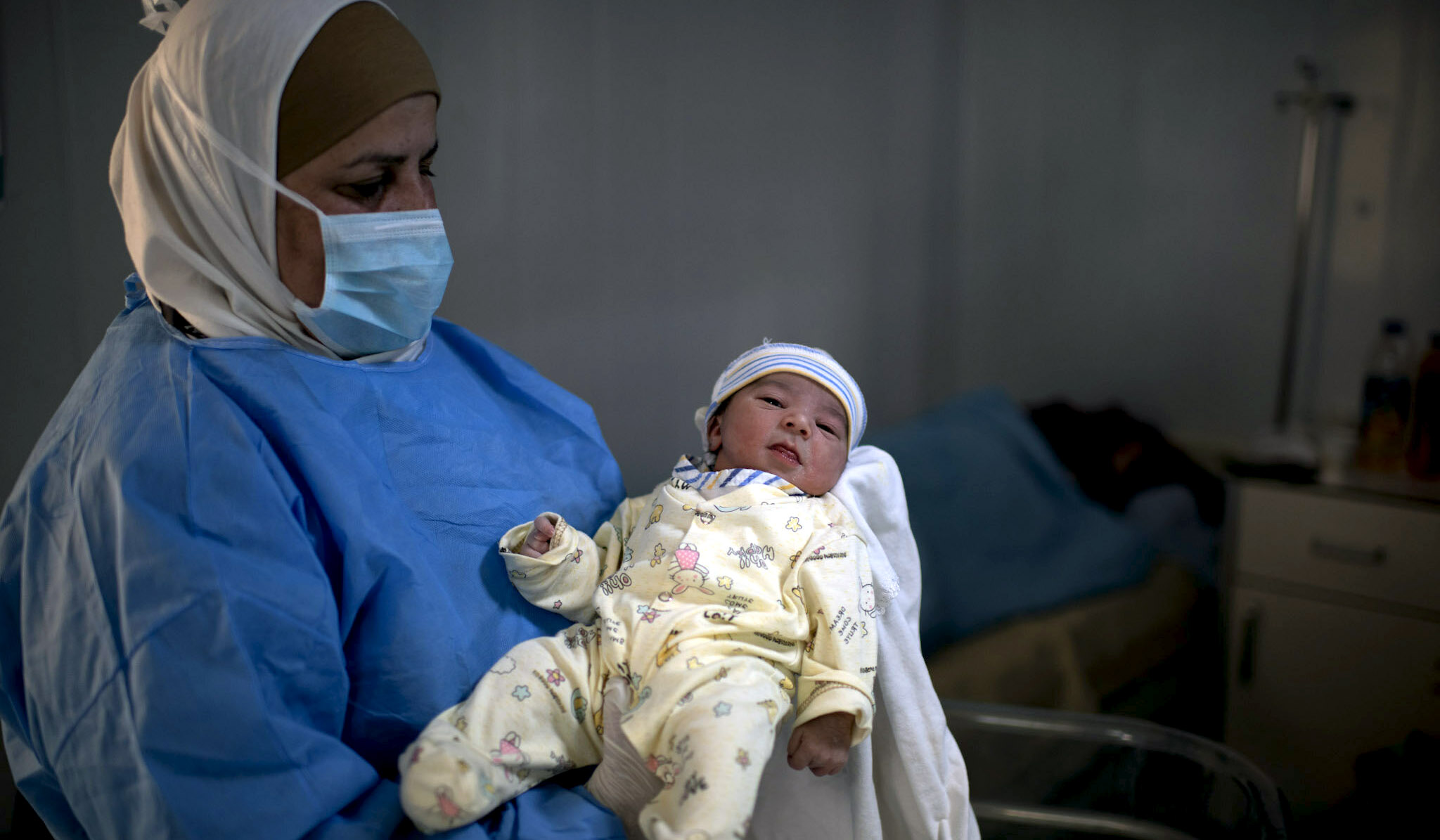 Medical staff at a medical facility at the Azraq Camps holds up a newborn baby.