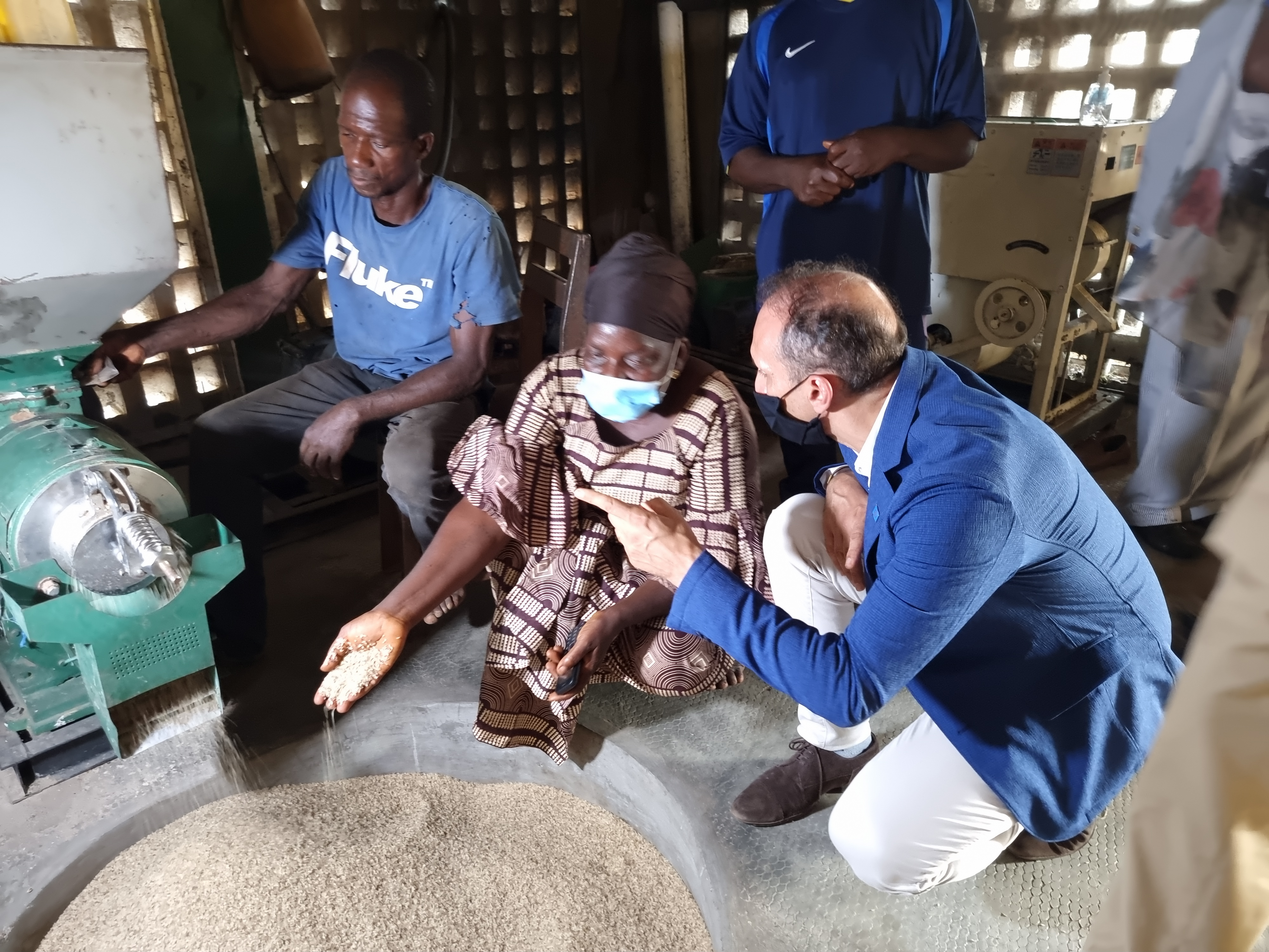 Resident Coordinator, Vincent Martin kneels by a woman community leader as they speak near a machine that is filling a round hole with grains.