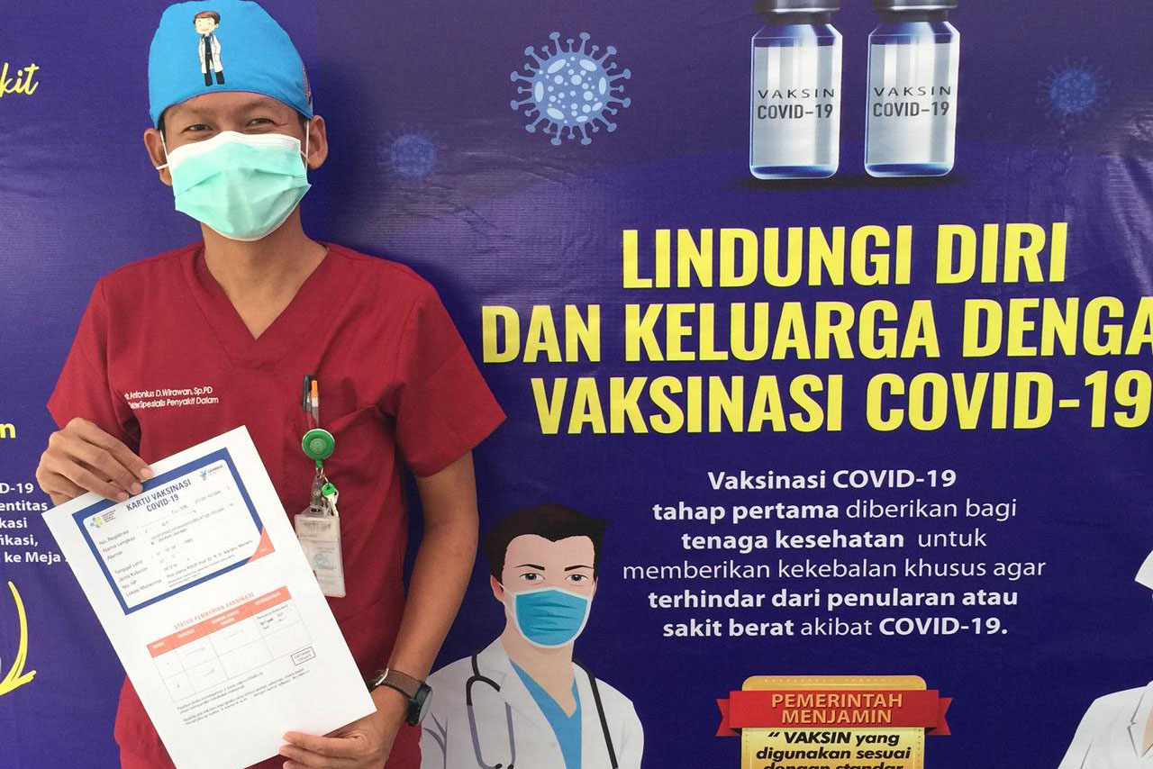 Dr Antonius Irawan stands in front of a COVID-19 vaccination poster holding his COVID-19 vaccination certificate after he received his first dose of COVID-19 vaccine at Dr Kandou District General Hospital .in Manado City, North Sulawesi Province