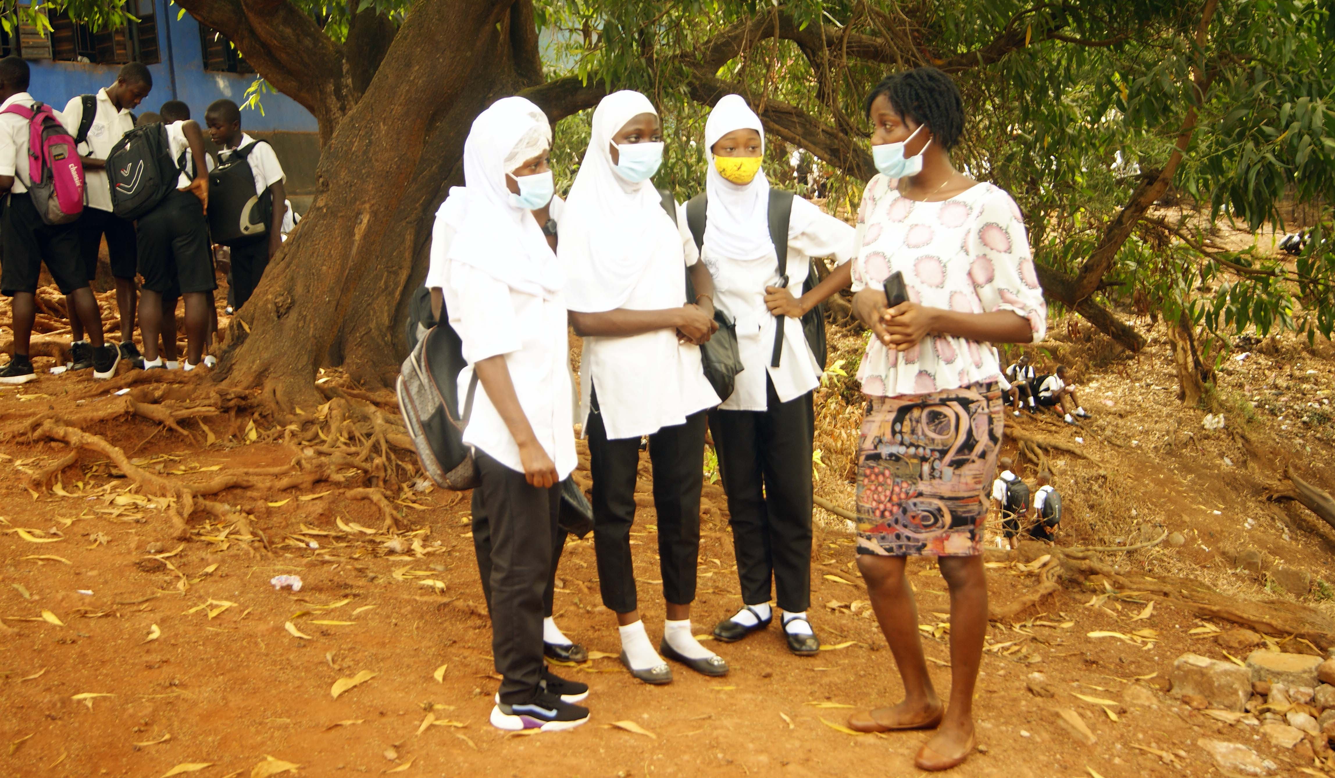 A woman wearing a face mask stands and speaks with three adolescent girls.