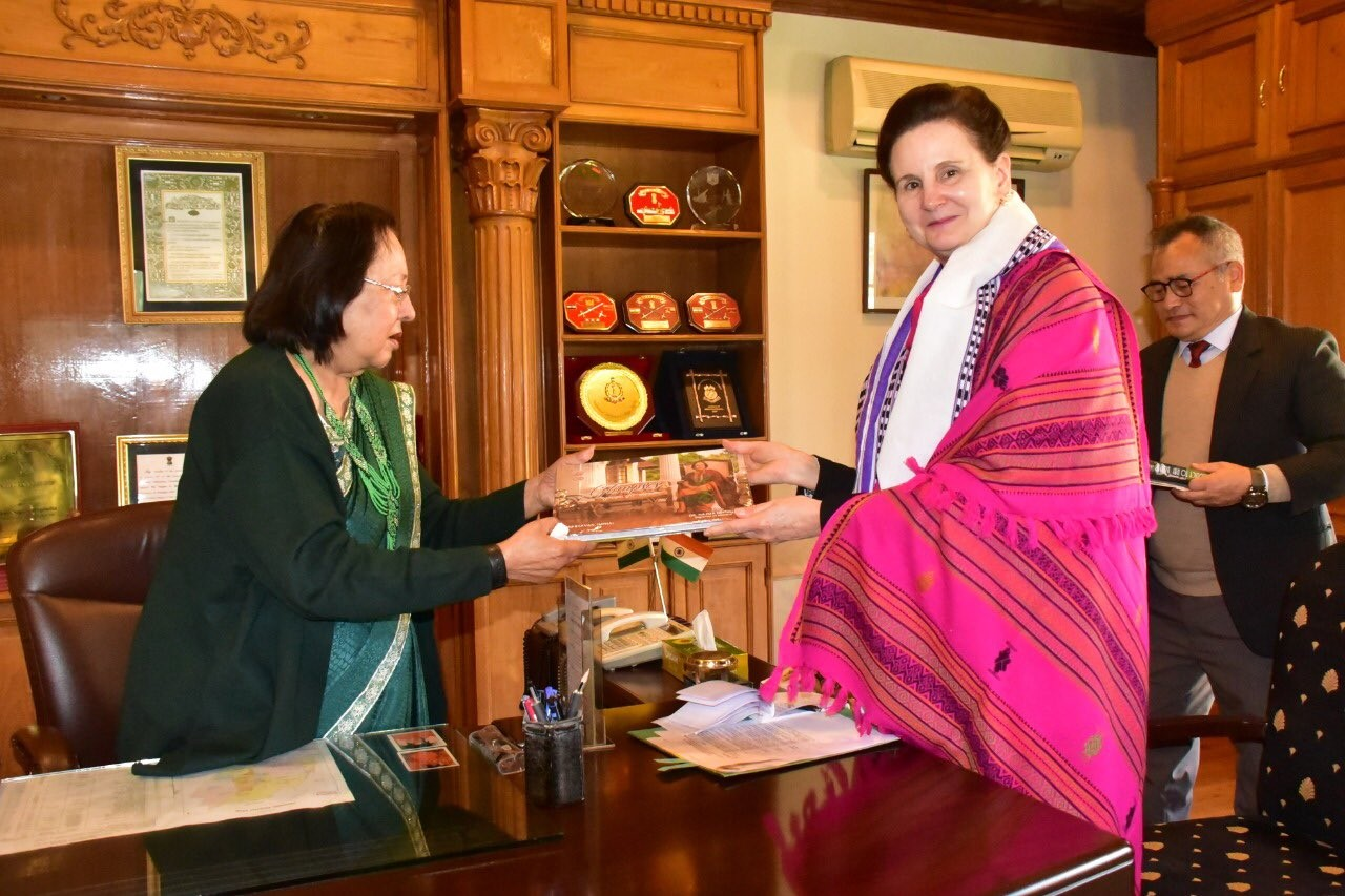 The governor of Manipur, on the left wearing a green dress, gives a document to the RC India, on the right, wearing a pink traditional clothe