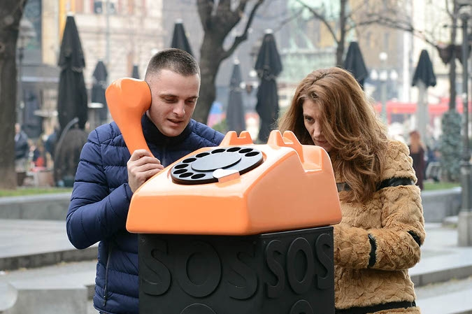 A man and woman stand next to a large orange telephone while the man holds the receiver.
