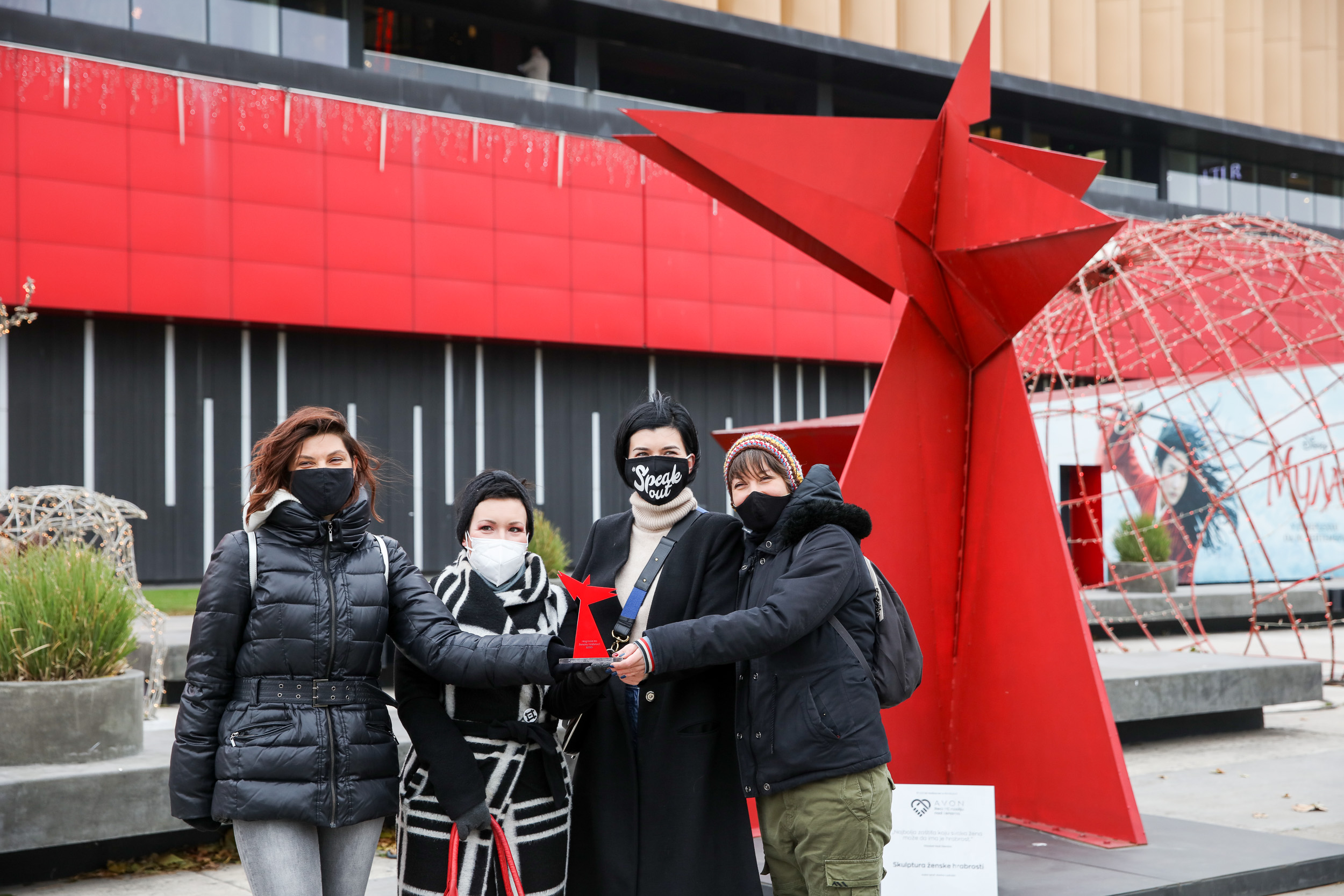Four women stand together with masks in front of a red statute.