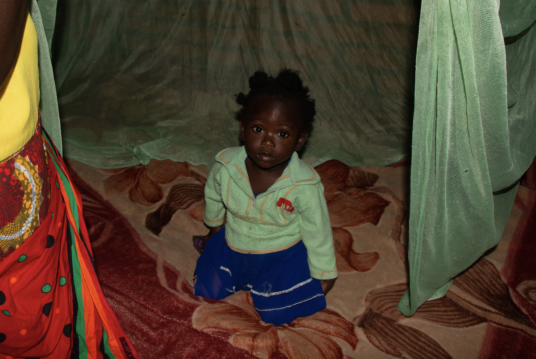 A young girl in a green sweater and shorts sits under a green mosquito net.