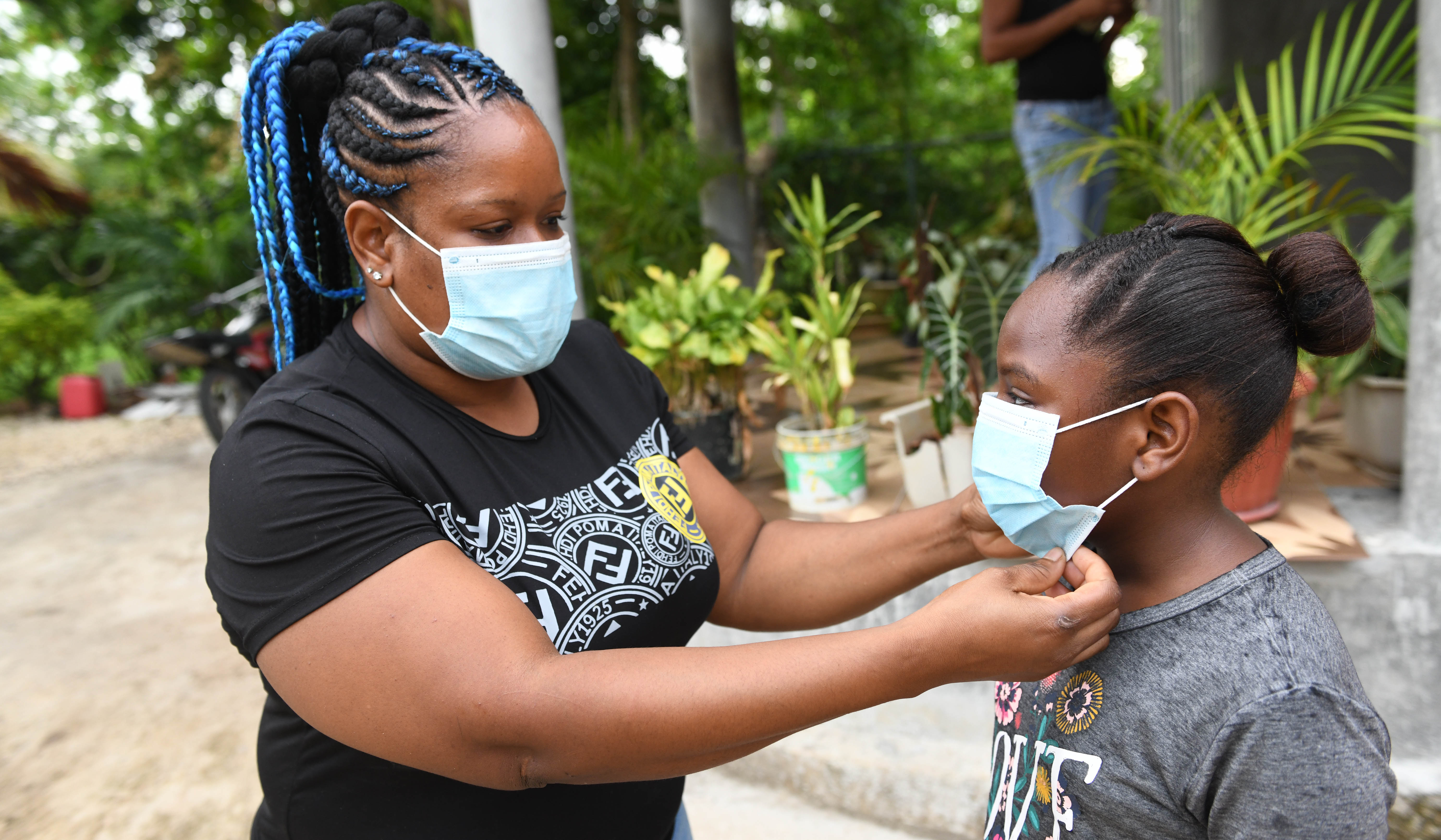 Kaedia Ellis Johson adjust the face mask for her daughter Sasheena Johnson astudent of Little Bay Primary and Infant School. On Monday, September 7,2020. Little Bay is a mainly fishing community located in the parish of Westmoreland, the western end of the island of Jamaica.