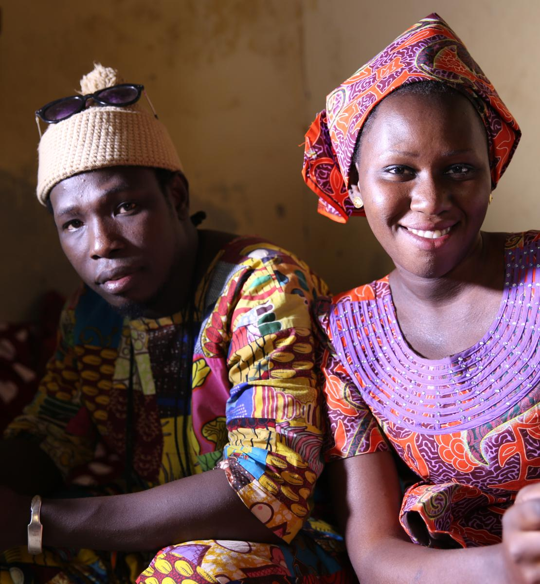 Two Senegalese youth, a young man and woman, proudly looking at the camera while holding their mobile phones.