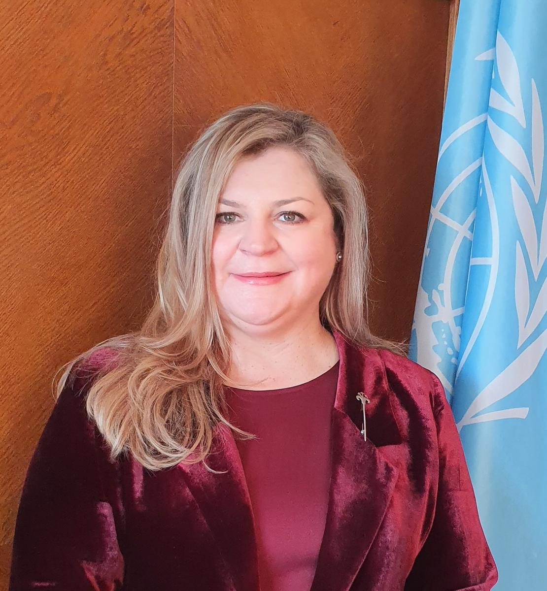 Official photo shows Catherine smiling to the camera, wearing a wine coloured jacket and blouse. She stands by the UN flag.
