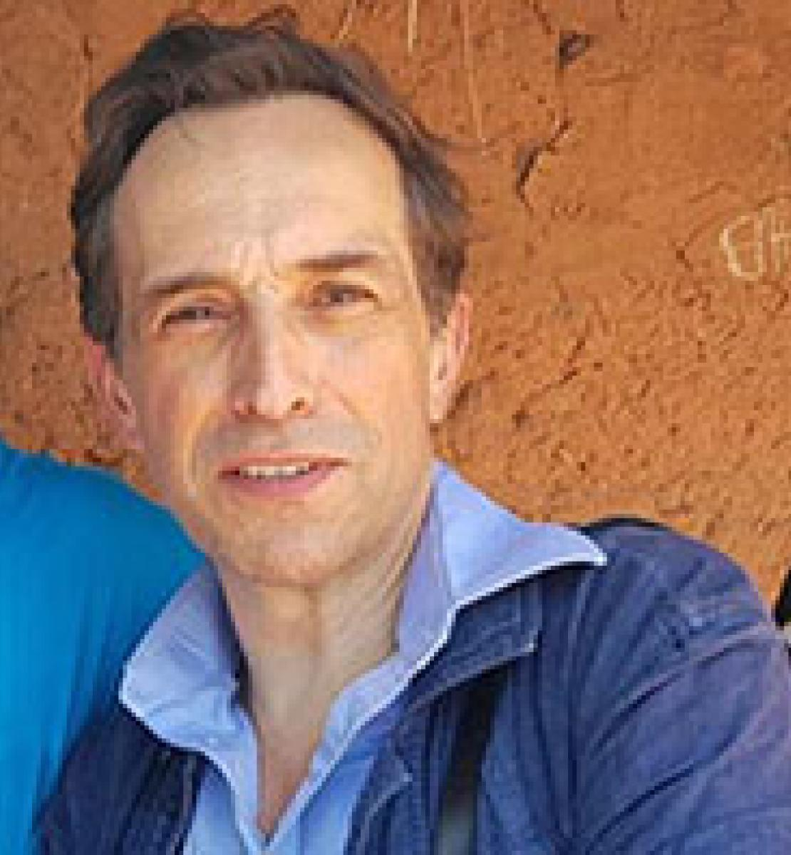Photo shows Julien leaning towards the shoulder of another person. He's wearing a denim jacket, blue shirt and stands in front of a mud-coloured cement wall.