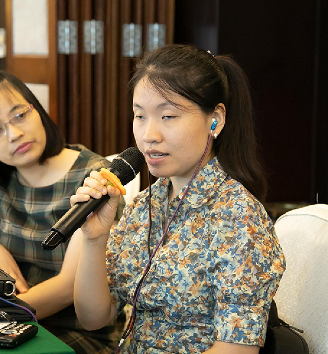Banner shows Huong Dao Thu speaking into a microphone at a table with two women beside her.
