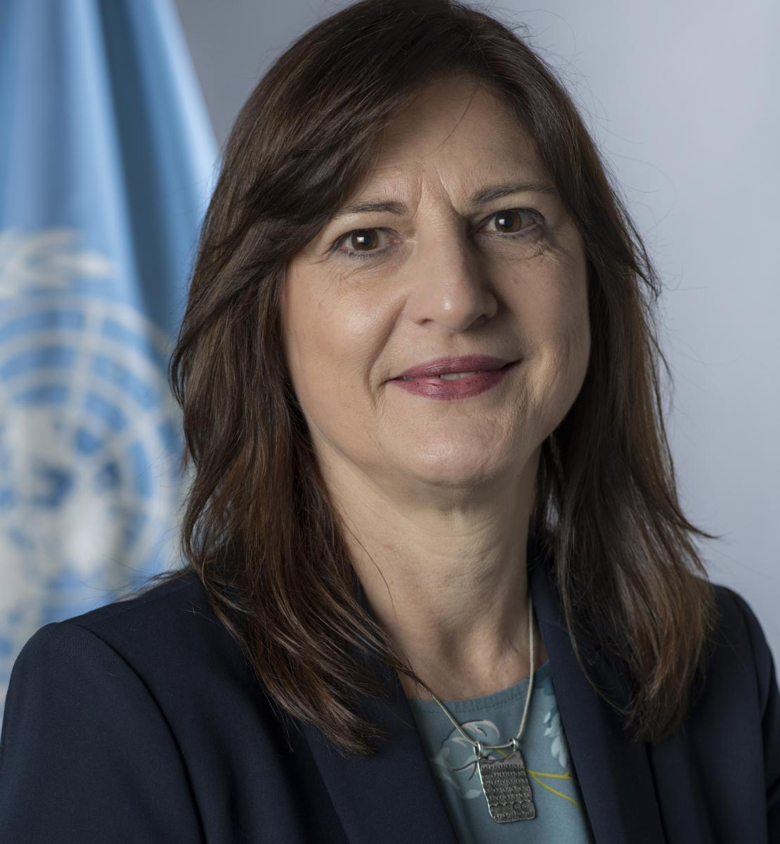 official photo of Susana Sottoli shows her standing in front of the UN flag.