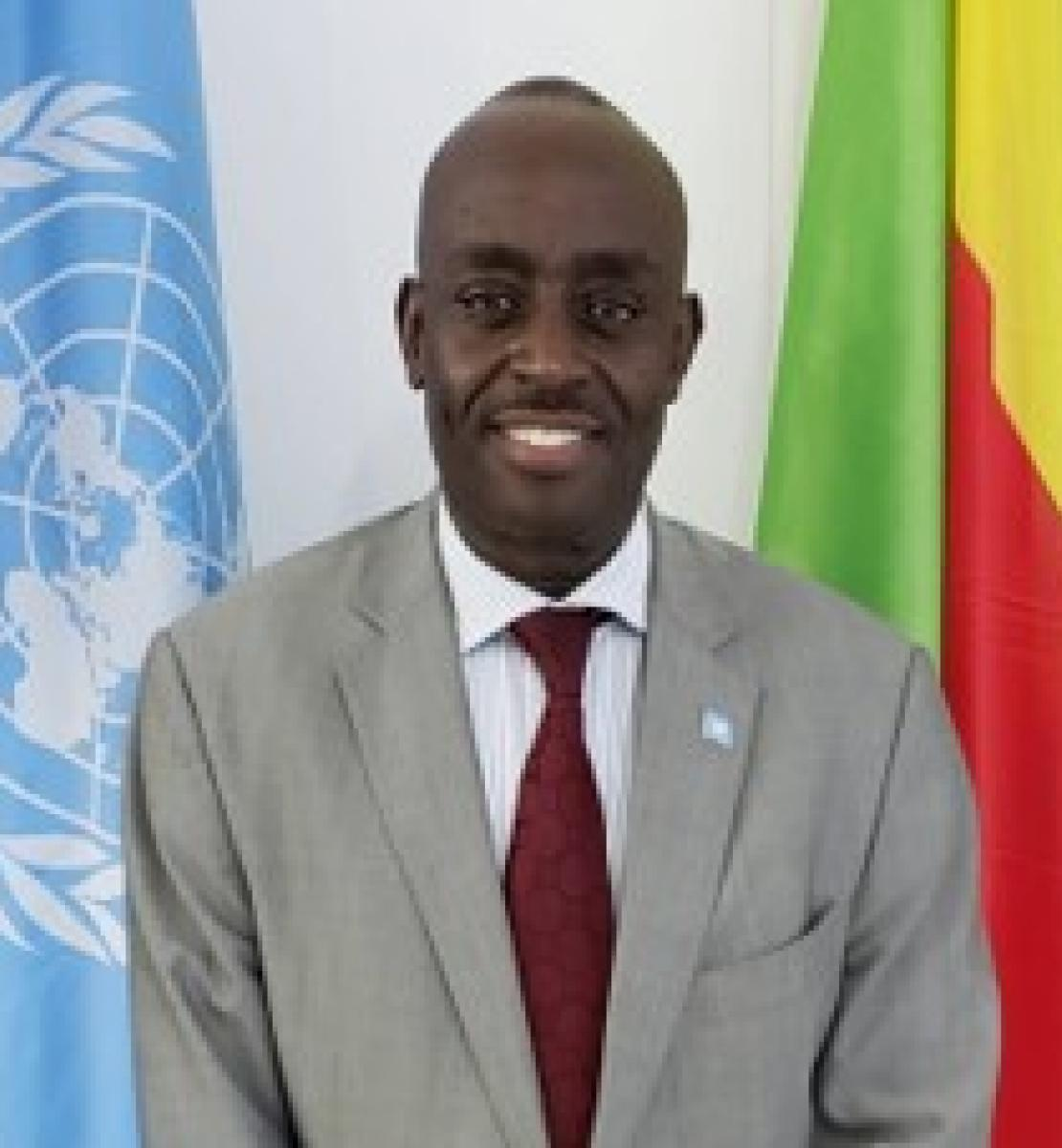 Official photo of Chris Mburu standing in between the UN and DRC flags.