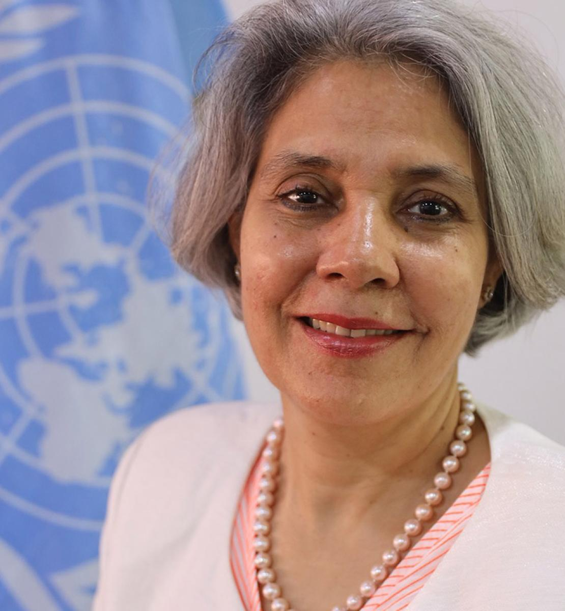 Official photo of Gita Sabharwal. She is shown smiling in front of the UN Flag.