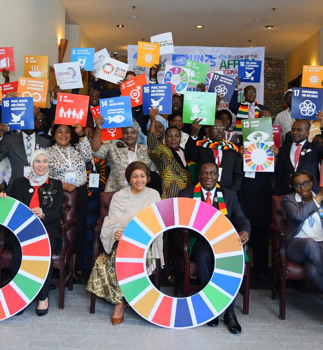 Shows DSG sitting with Resident Coordinators and colleagues holding SDGs signage.