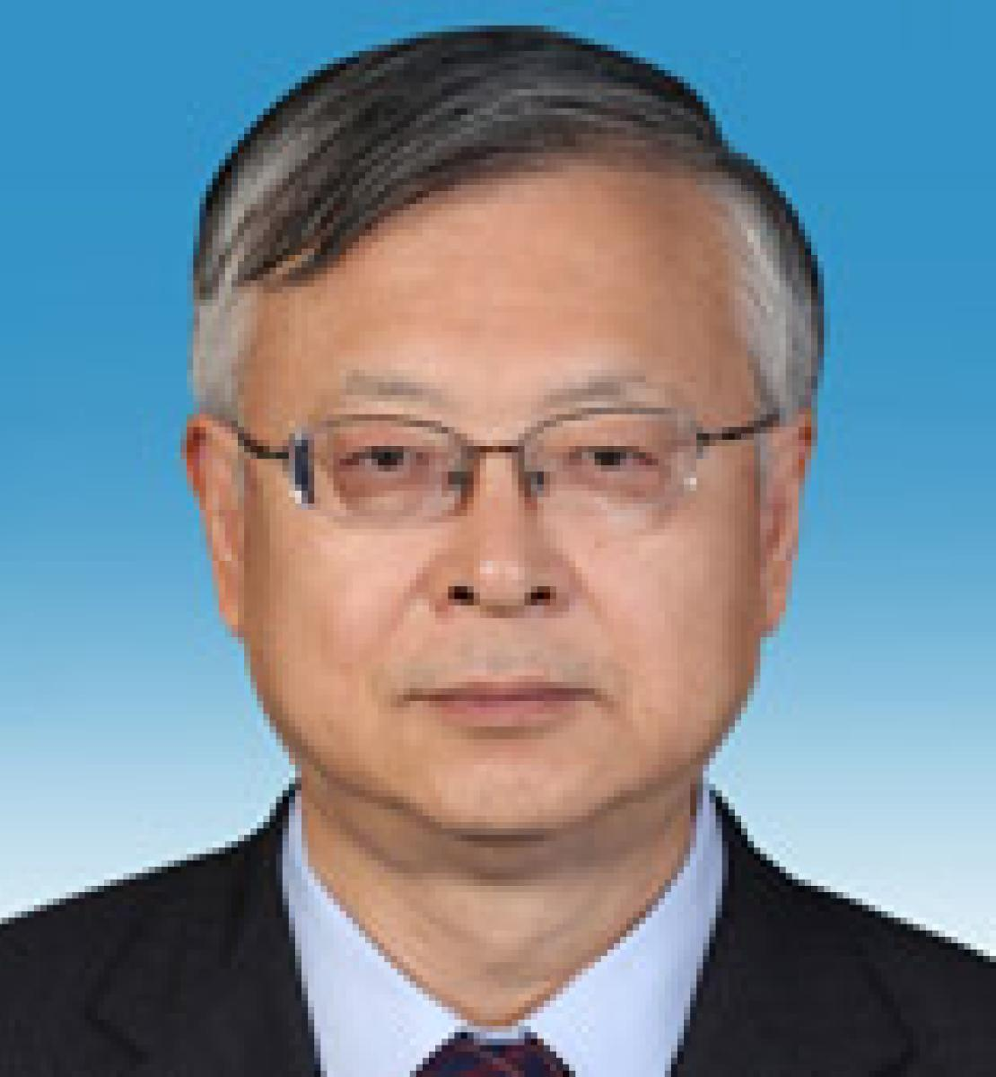 Head-to-shoulders close up of Sen Pang. He wears a dark suit, glasses and stands in front of a gradient blue background.