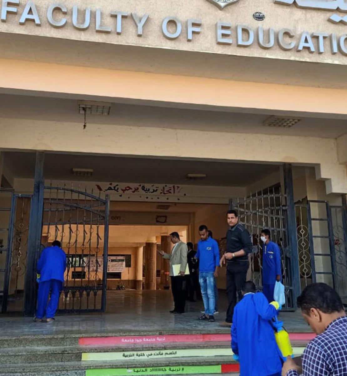 Shows men in protective gear cleaning the steps of the Faculty of Education.
