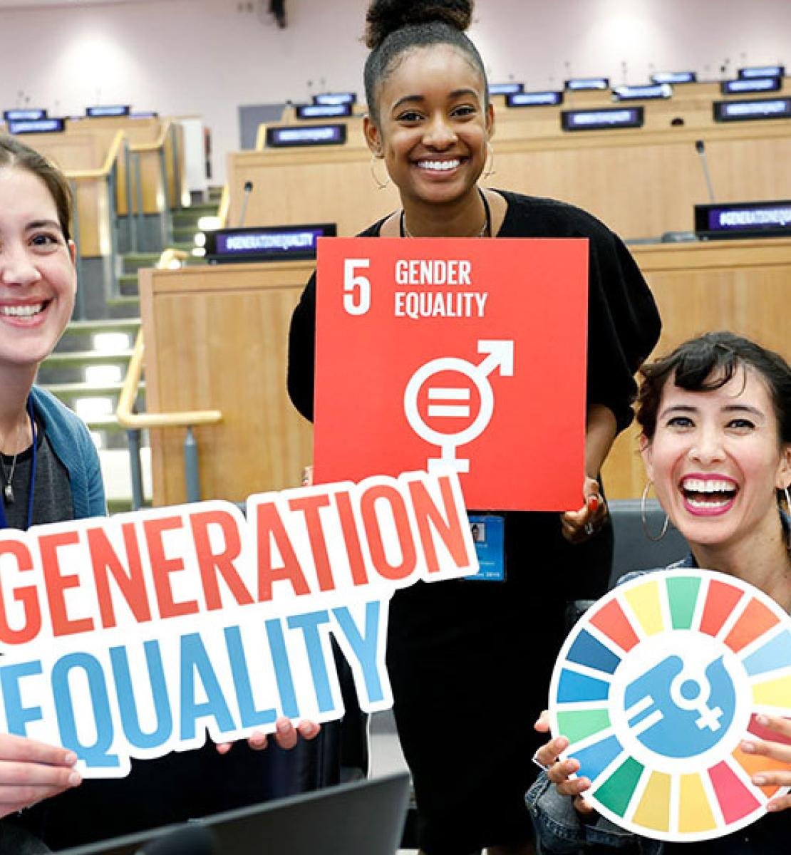 Young women hold SDG and Generation Equality signage.