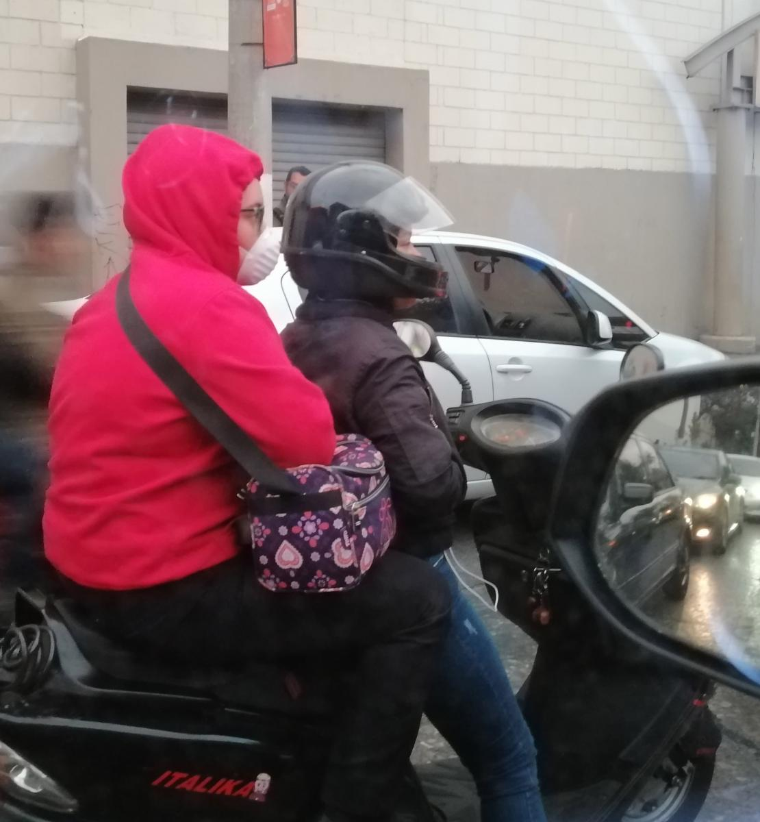 View of two people riding a motorbike wearing protective masks.