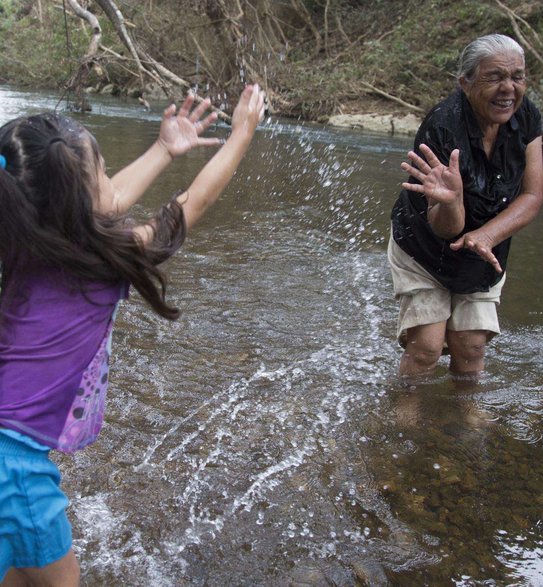 Four-year-old Allizon Stefany Escobar splashes her laughing great-grandmother, Conzuelo Flores, as they stand in shallow water at a river near their home, in Cayo District.