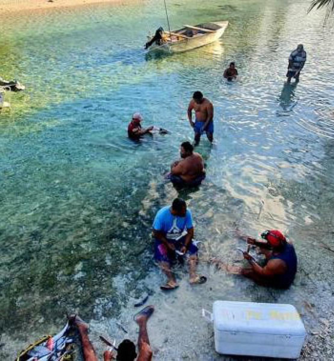 Shows people by the shore of the islands of Tokelau.