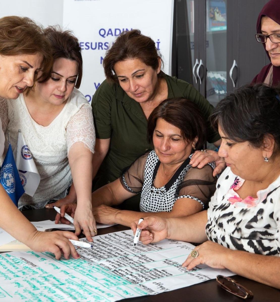 Plusieurs femmes sont regroupées autour d'une table sur laquelle est posée une très grande feuille papier portant des inscriptions. Certaines de ces femmes tiennent un stylo-feutre à la main.