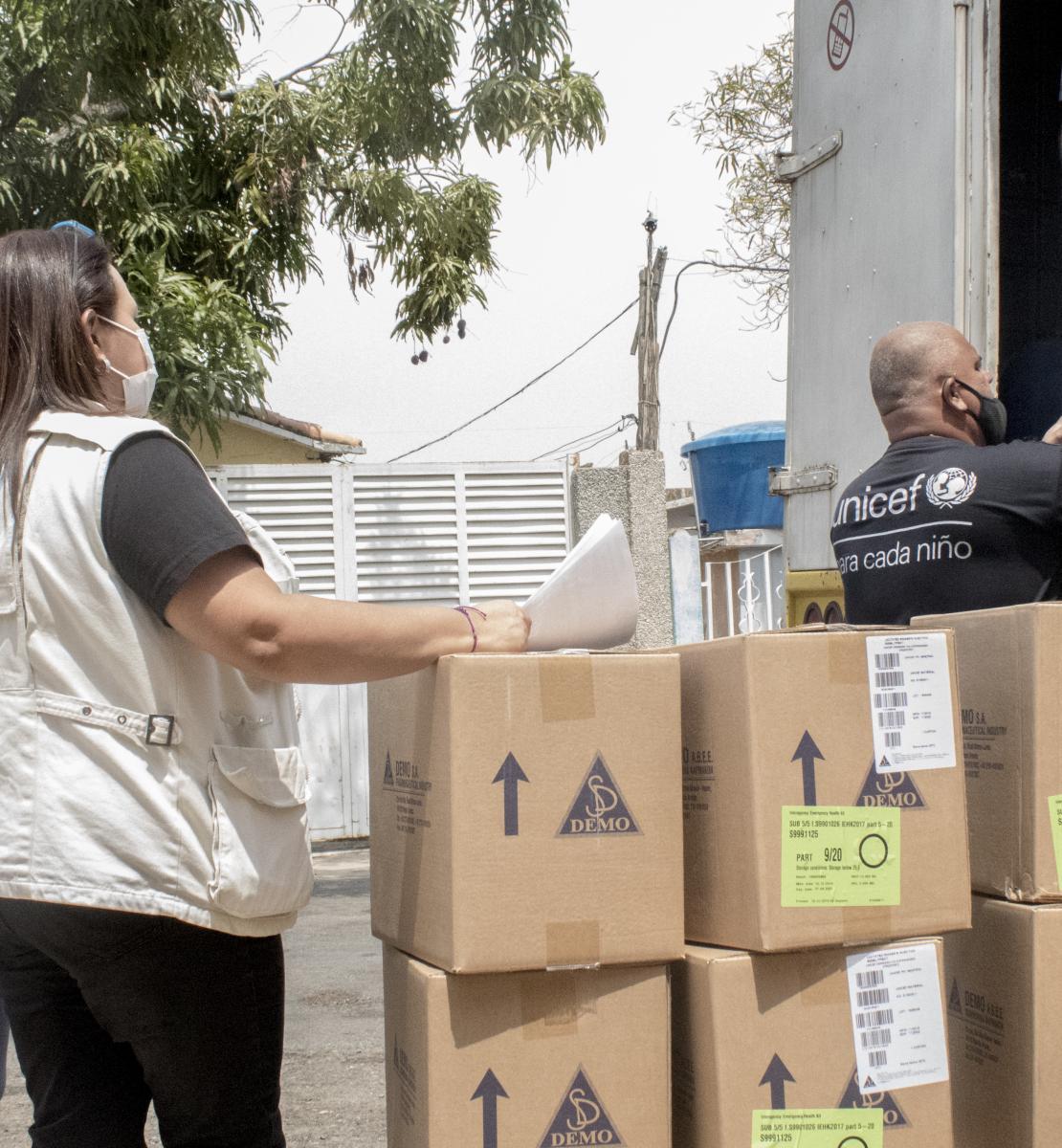 Un membre masculin du personnel de l'UNICEF portant un masque de protection aide à décharger des cartons dans le cadre de l'opération d'aide humanitaire réalisée au Venezuela. Deux femmes portant un masque de protection se tiennent debout près des cartons déchargés.