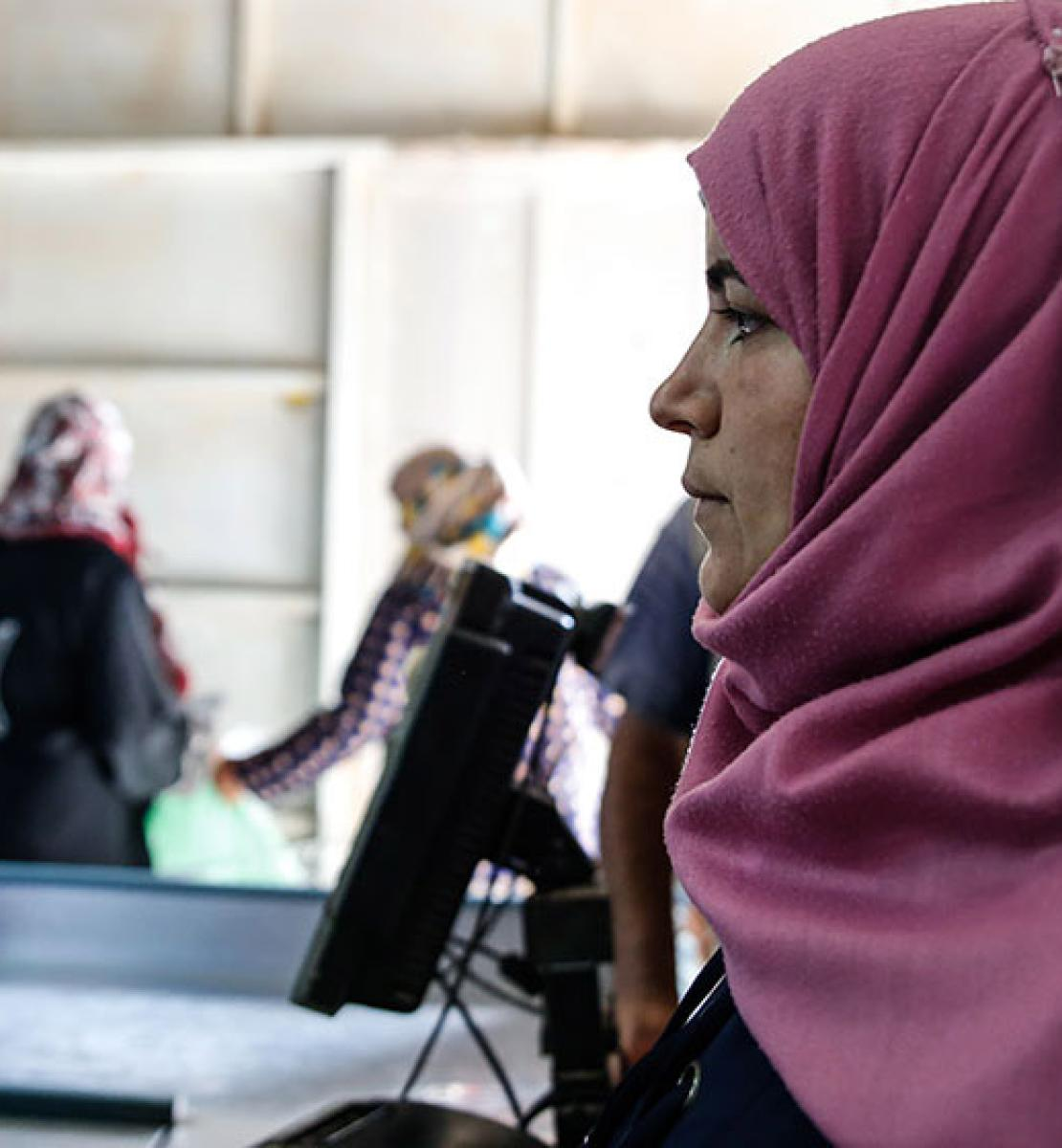 A UN Women beneficiary gets her iris scanned, allowing her to buy groceries at the Sameh Mall Supermarket in Azraq refugee camp, Jordan.