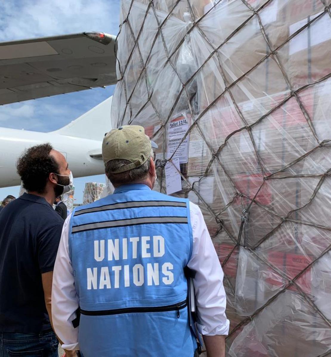 Une troisième cargaison de fournitures essentielles destinées à sauver des vies arrive au Venezuela. Deux hommes, dont l'un porte un gilet bleu des Nations Unies, se tiennent debout devant la cargaison, sur le tarmac de l'aéroport.