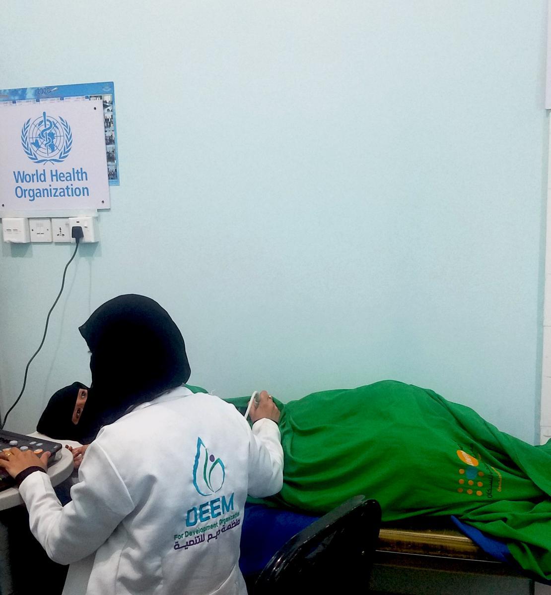 Una trabajadora sanitaria realizando una ecografía en el centro de salud de Al-Wadhah en Taiz.