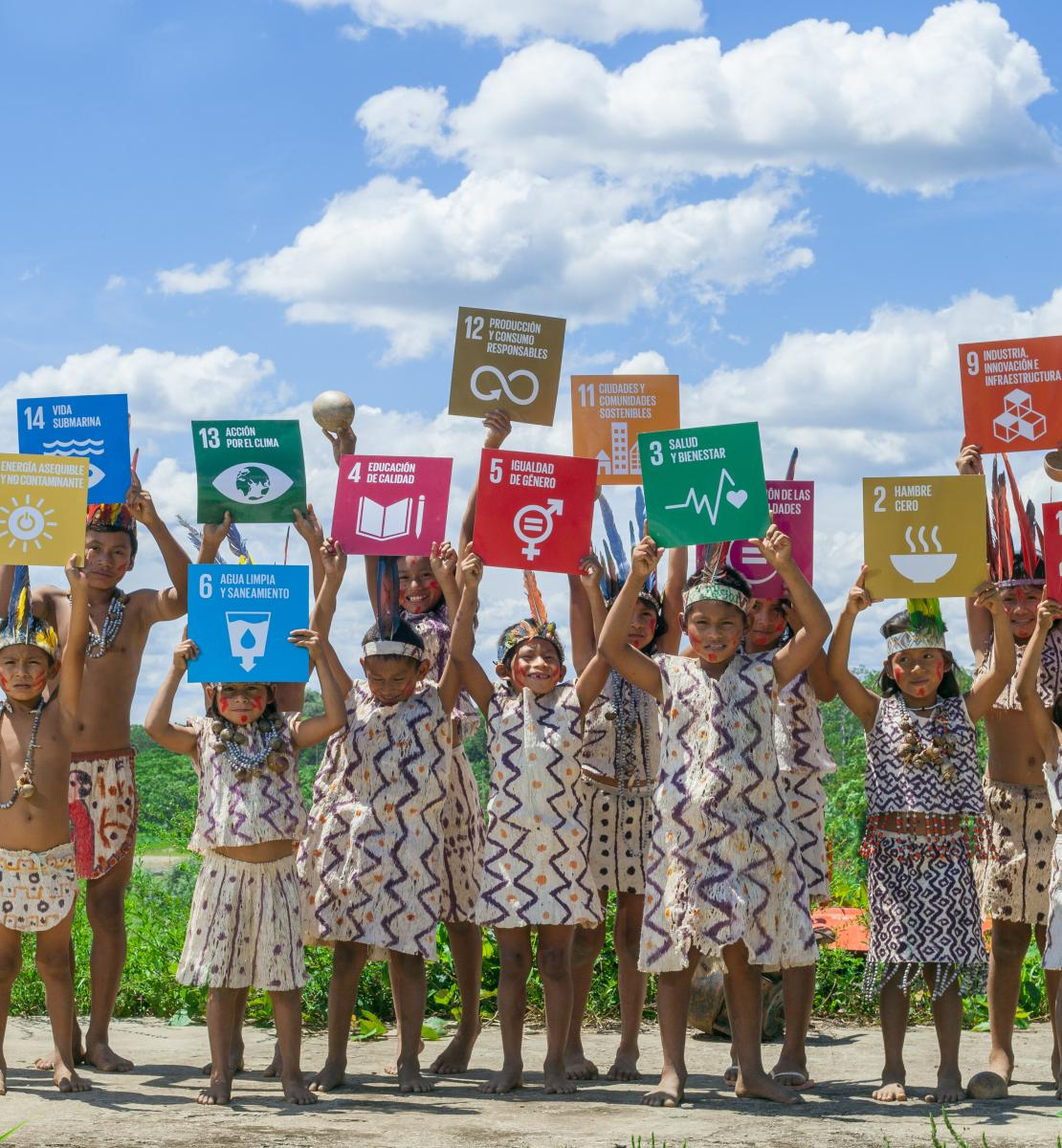 Young indigenous children wearing brightly coloured outfits proudly hold up SDG signage.