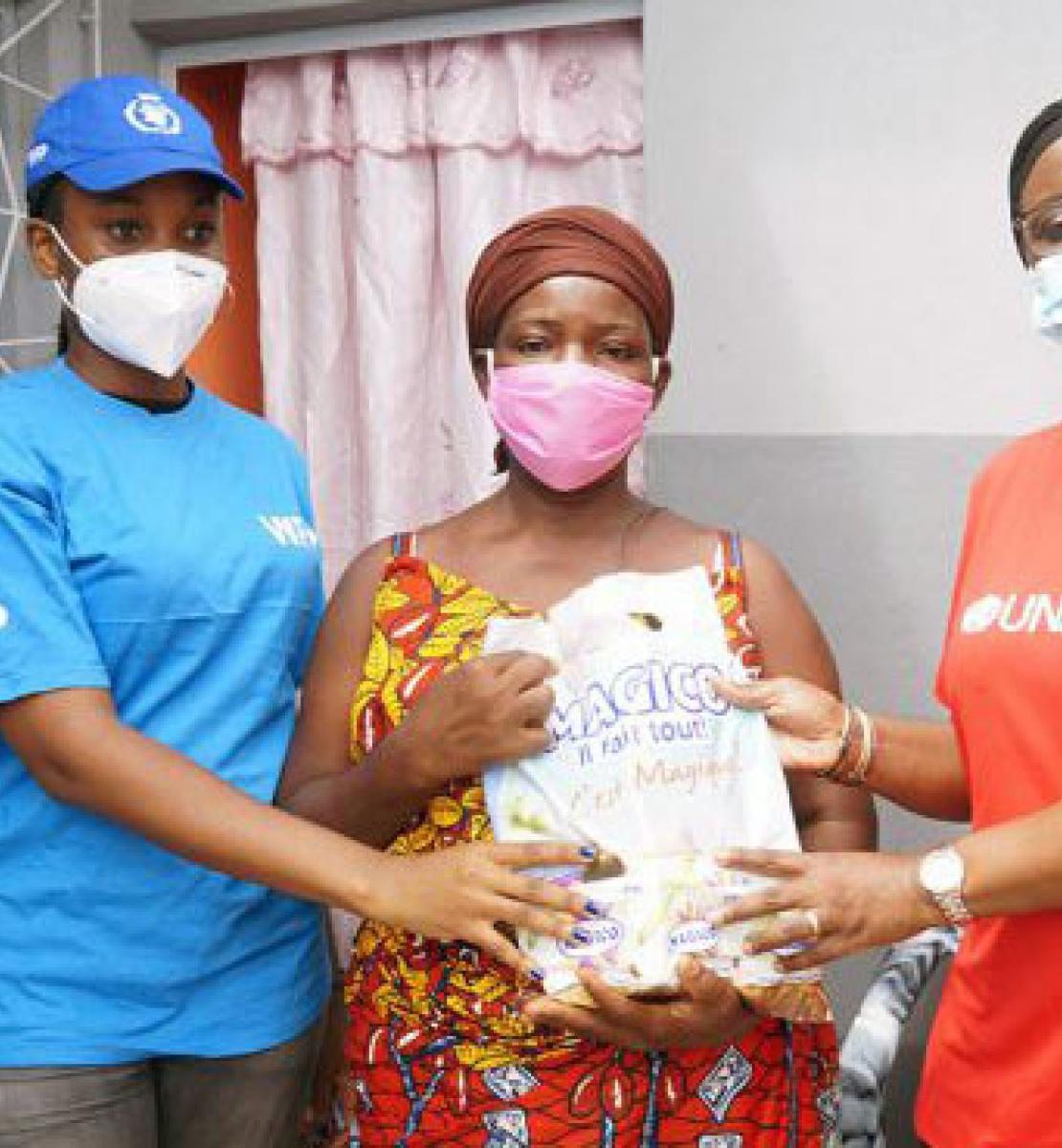 WFP and UNAIDS staff stand besides a woman holding a bag of essential supplies.