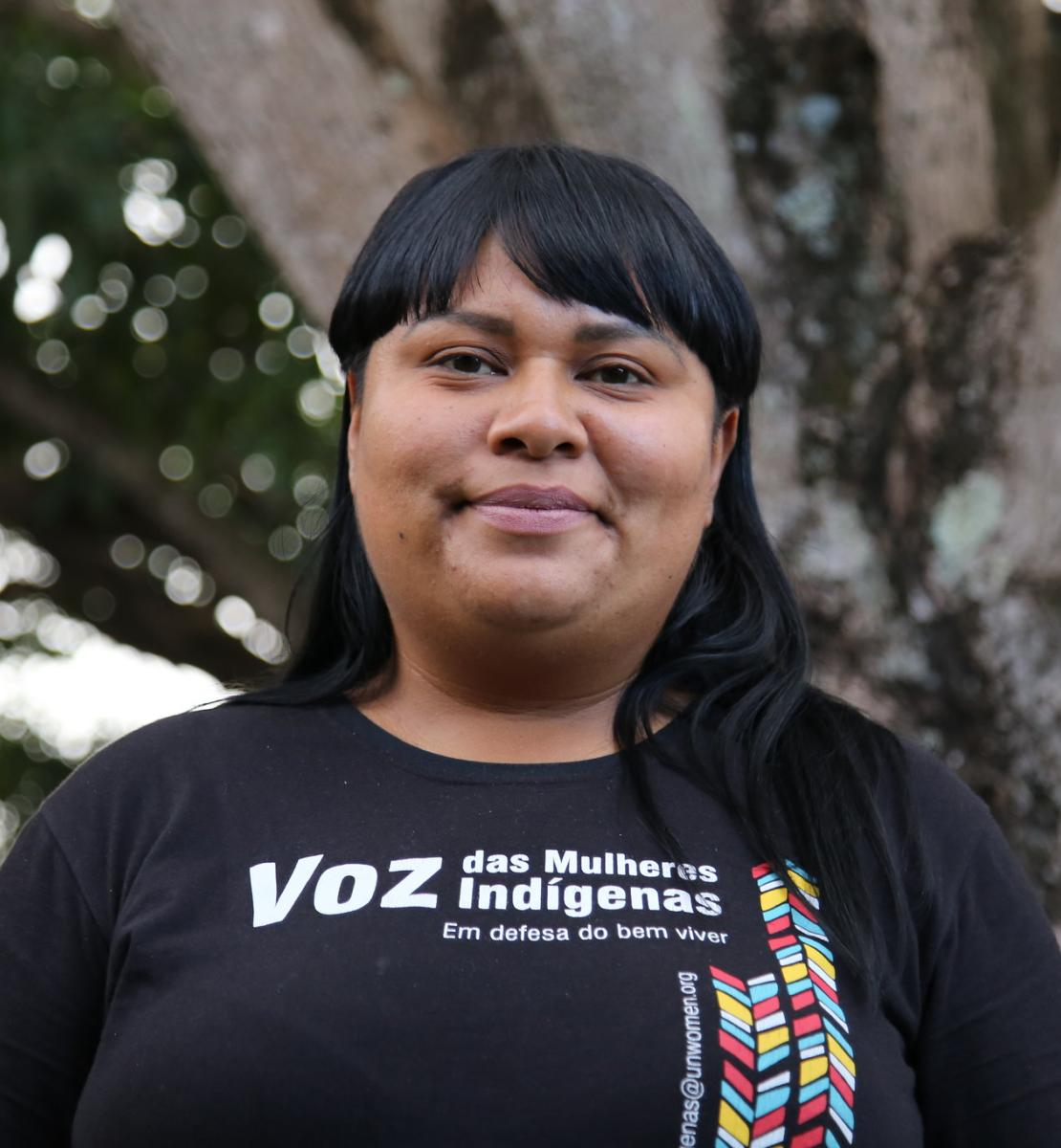 An indigenous woman smiles proudly wearing a t-shirt that reads Voice of the Indigenous women