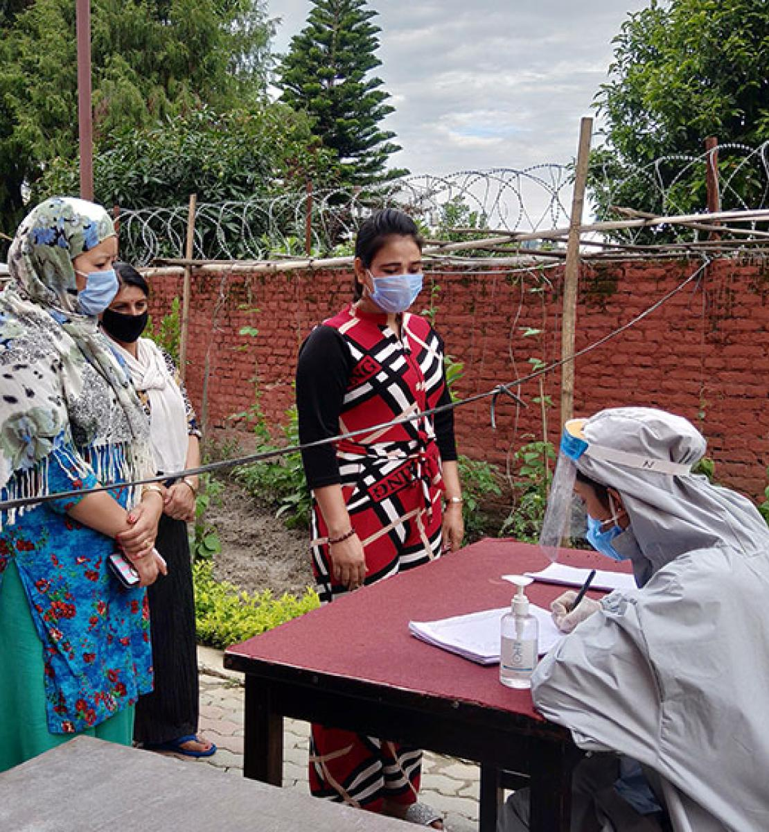 Women wait in a queue to get their temperature checked by staff at WHR's women-managed quarantine facility.
