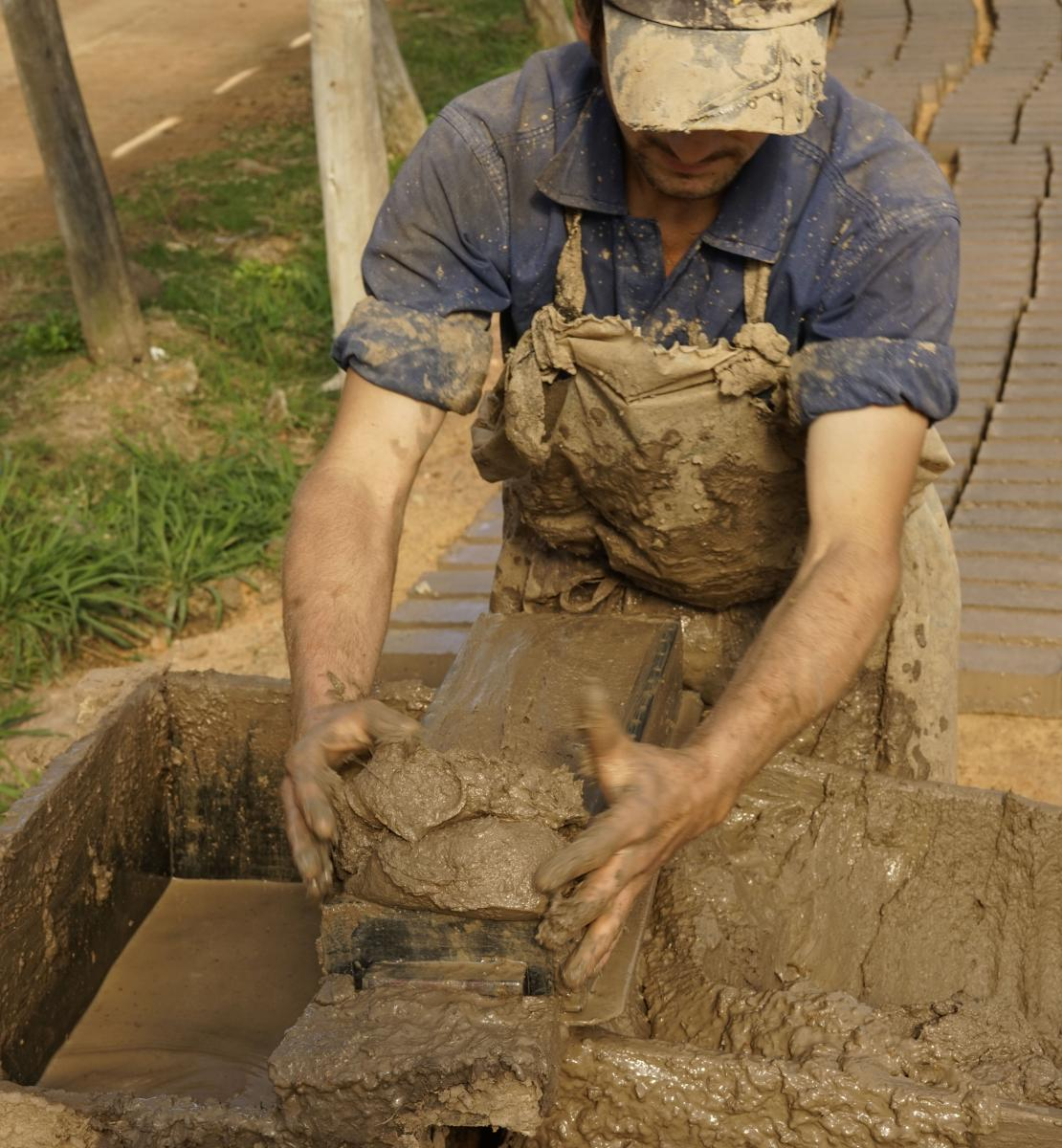 Photo shows a brickmaker molding bricks by hand.