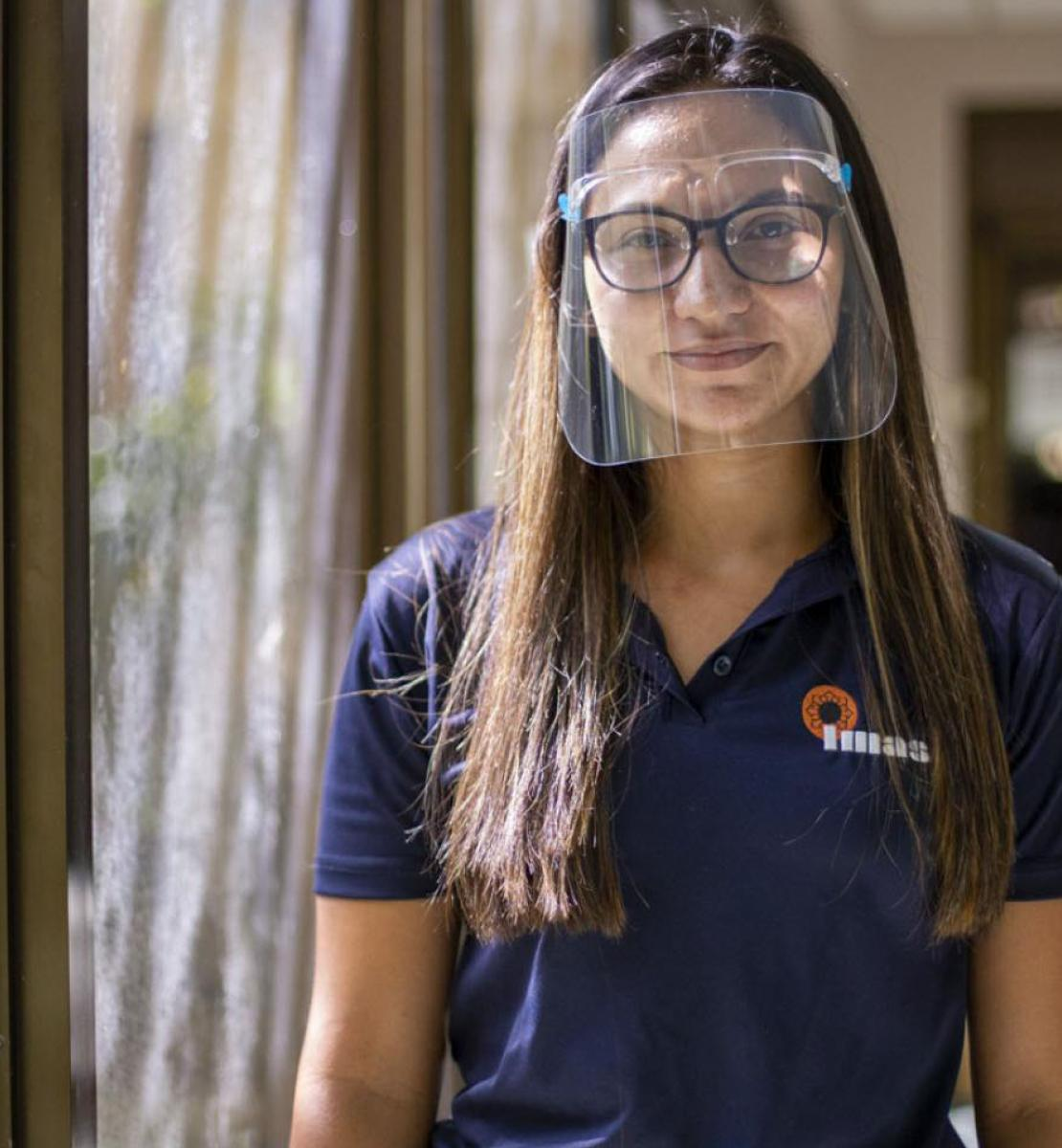 Gabriela Gamboa stands by an glass door wearing a protective face shield.