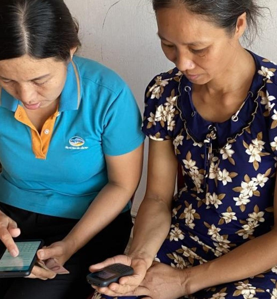 Mrs. Man (right) learns from Viettel Pay staff how to use e-payment technology on her phone to receive Government's Social Assistance package for COVID-19