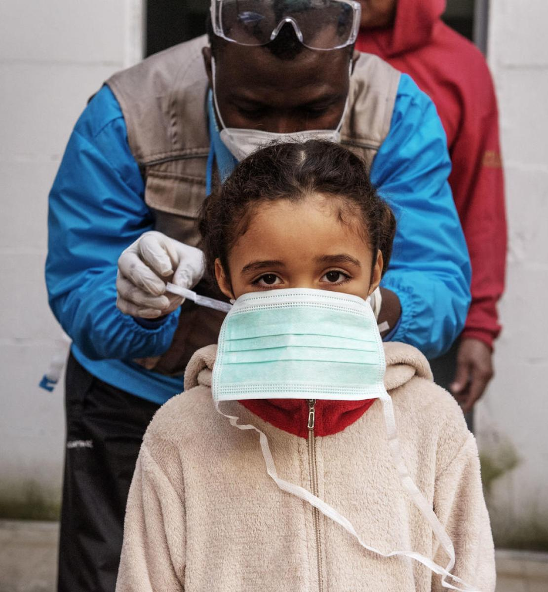 A seven-year-old girl is given a protective mask by INTERSOS/UNICEF outreach worker.