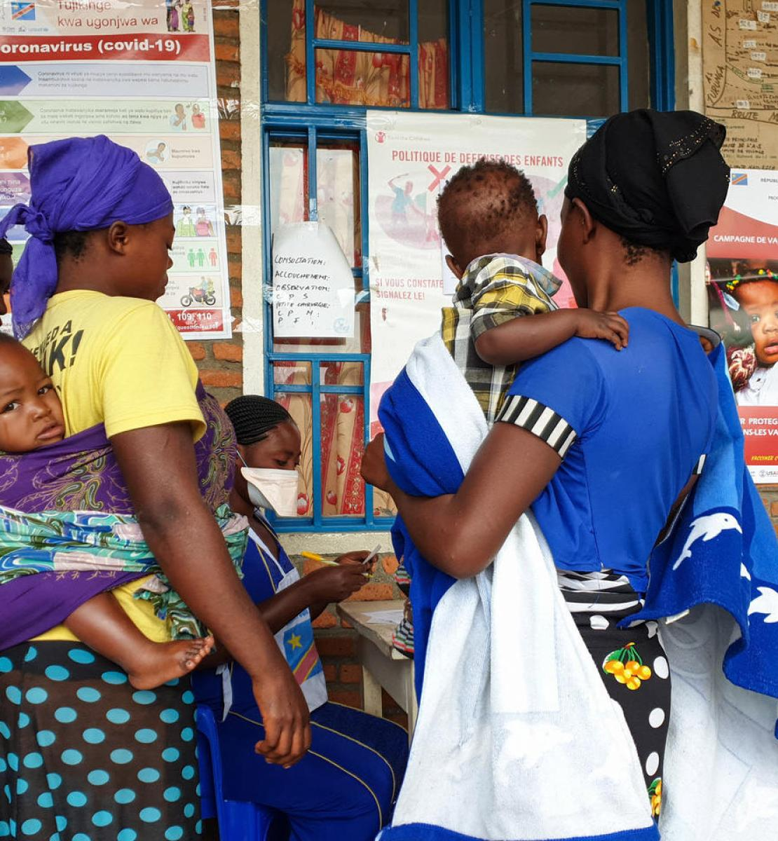 Women with their babies stand outside a medical facility reading signage on COVID and vaccinations.