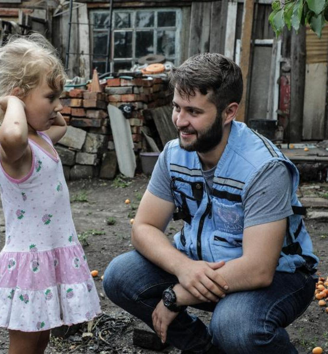 UN staff kneels as he smiles and speaks with a little girl in Ukraine.