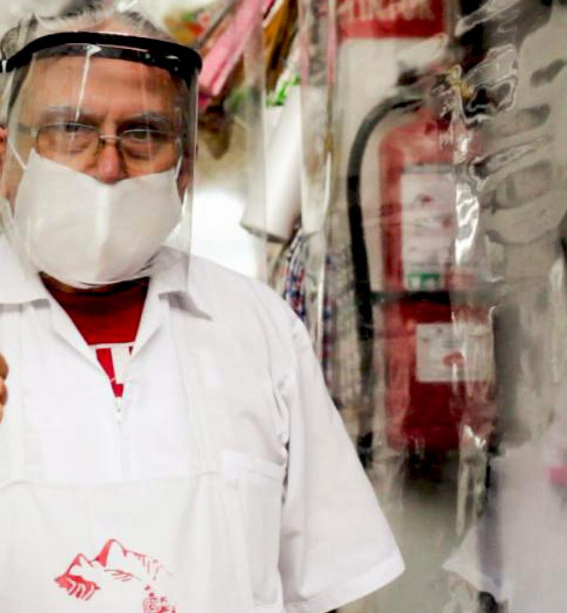 A vendor wearing a protective mask and life shield gives us a thumbs up as he stands near his plastic covered shelves of products.