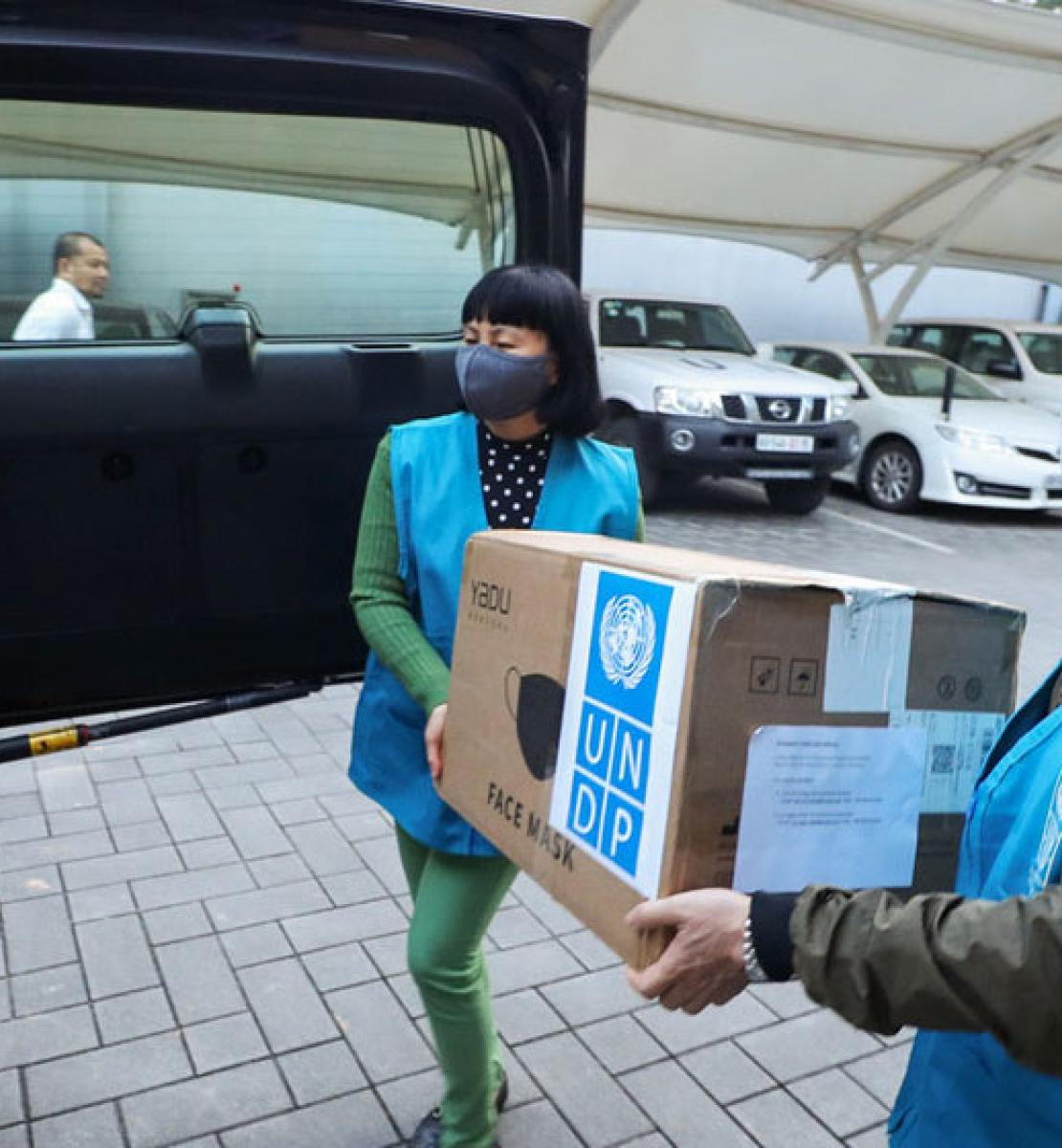UN staff carry a box of supplies to a vehicle for distribution.