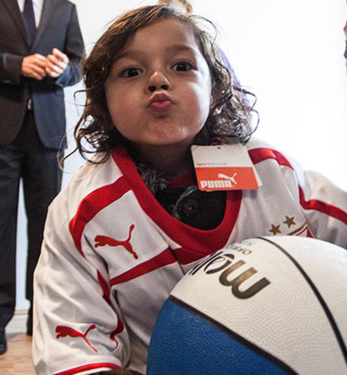 A little boy holds a basketball and puckers his lips at the camera.