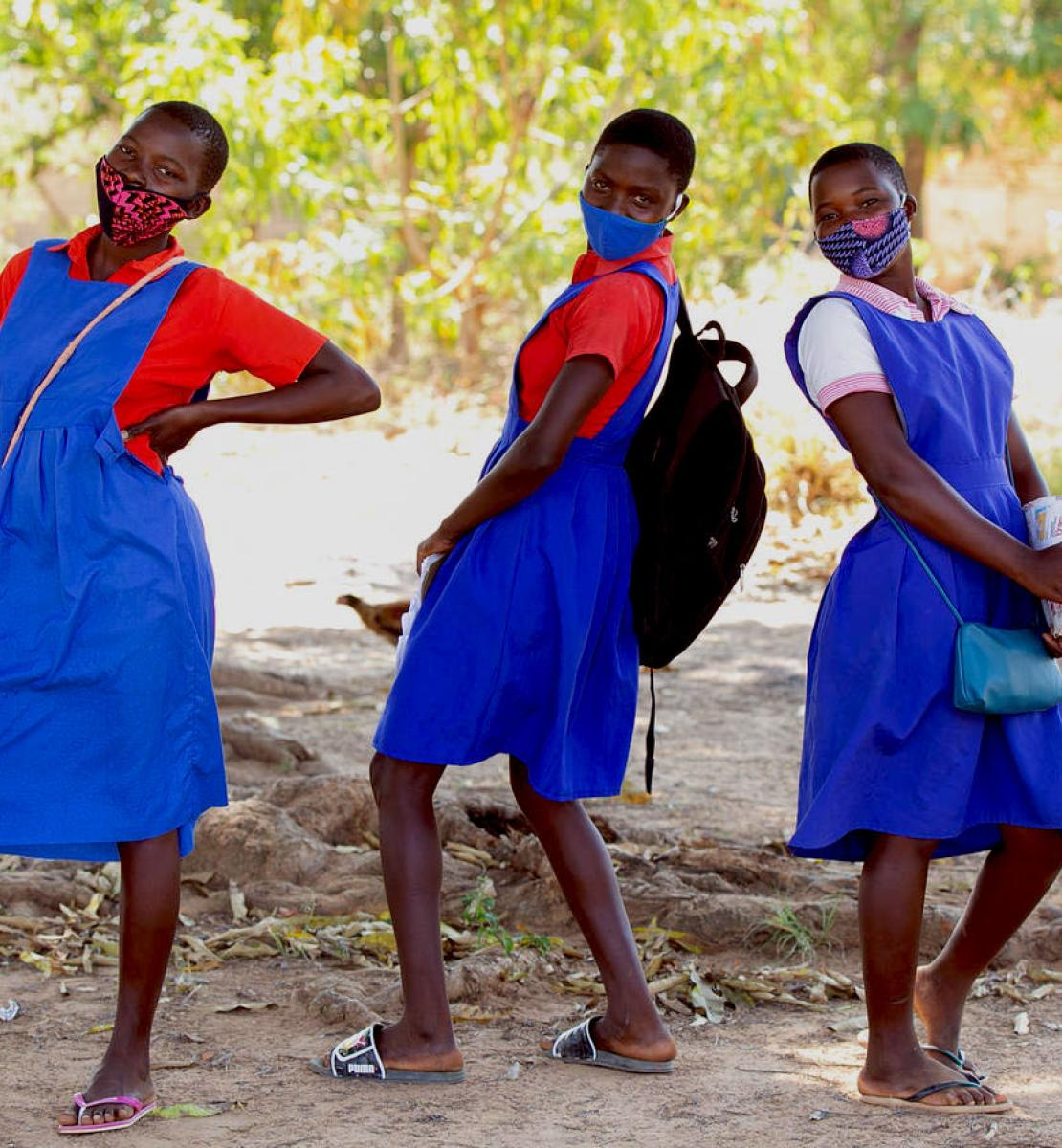 Three school girls having fun within the school campus at Luwambaza primary school