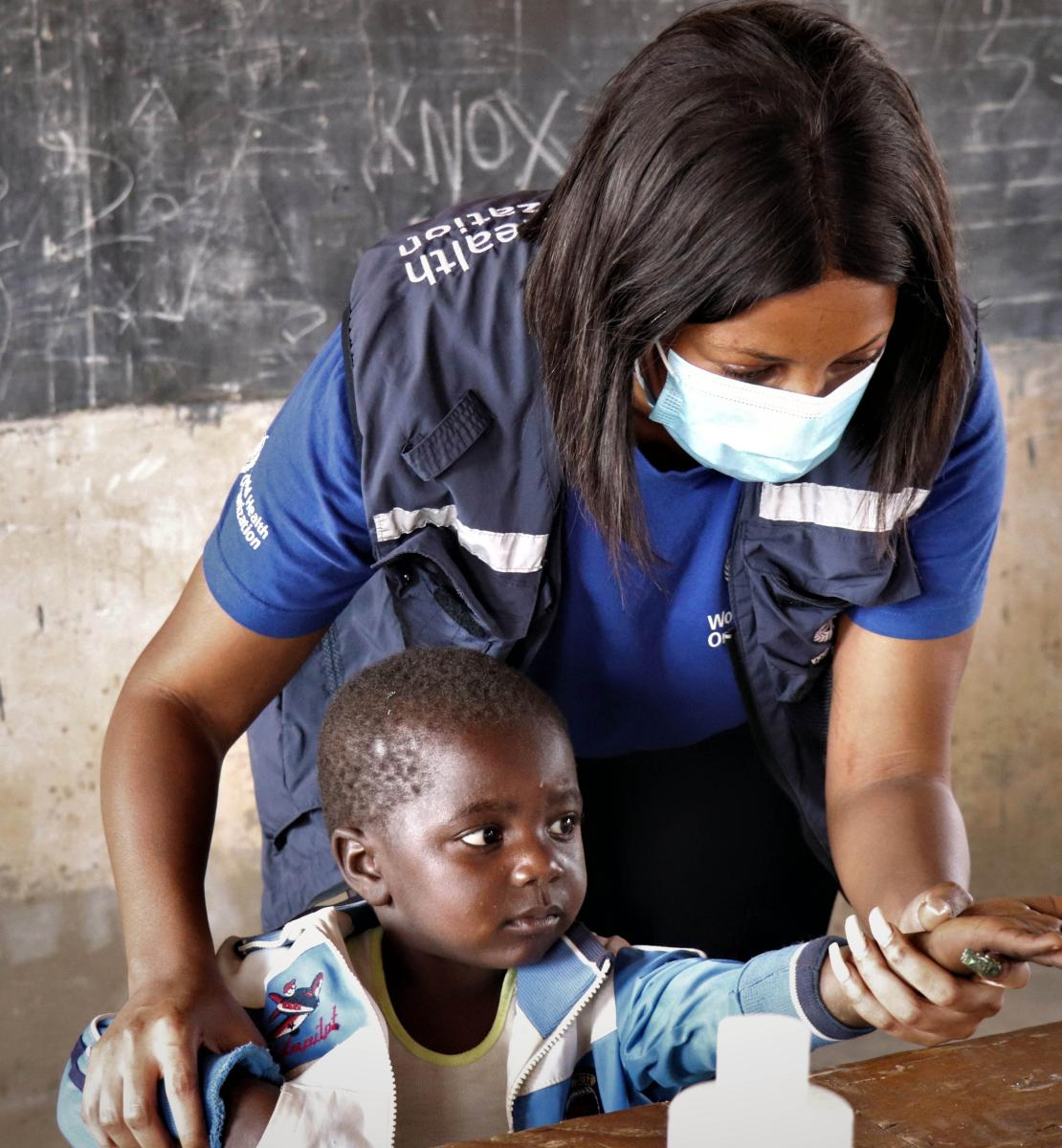 WHO staff helps a young boy hold out his hand as he is handed medicine in a local classroom in Zimbabwe.